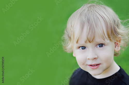 Valokuva Portrait of a blond curly-headed boy on green background, close-up, copy space