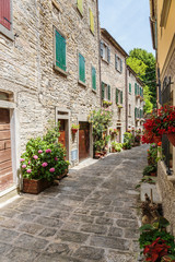 Fototapeta na wymiar Narrow old street with flowers in Italy