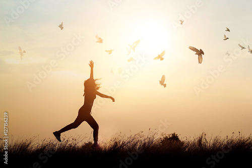 Woman and flying birds enjoying life in nature on sunset background