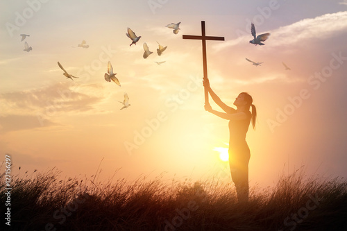 Canvas Print - Woman praying with cross and flying bird in nature sunset background