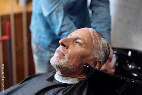 Fényképezés  Old man during washing his hair in barber shop