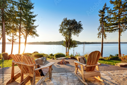 Back yard of waterfront house with adirondack chairs and fire pit Wallpaper Mural