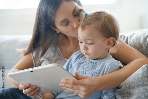 Fotografie, Obraz  Mother and daugther using digital tablet at home