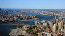 An Aerial Cityscape View Of New York City With East River And Brooklyn, Manhattan, Williamsburg And Queensboro Bridges Visible.