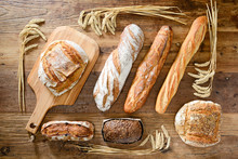 Assortment Of Traditional Loaf Of Bread And Baguette With Wheat On Wood Table Above View Flat Lay