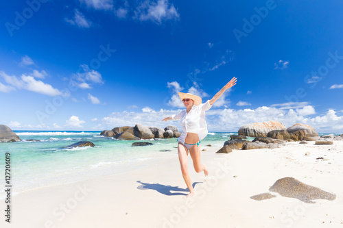 Poster Zanzibar Happy woman wearing white loose tunic over bikini and beach hat, enjoying amazing white sandy beach on Mahe Island, Seychelles. Summer vacations on picture perfect tropical beach concept.