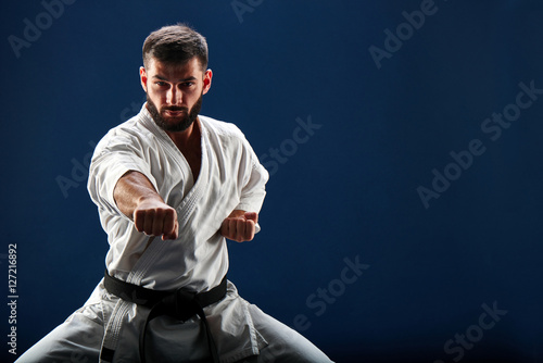 Fotomural Karate man in a kimono in fighting stance on a blue background