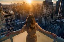 Rich Woman Enjoy The Sunset Standing On The Balcony At Luxury Apartments In New York City. Luxury Life Concept. Succesful B.businesswoman Relax.