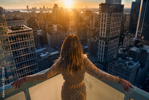 Rich woman enjoy the sunset standing on the balcony at luxury apartments in New York City. Luxury life concept. Succesful B.businesswoman relax. - 127228016