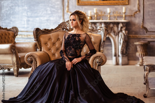 Tablou Canvas Beautiful young woman in gorgeous black evening dress with perfect makeup and ha