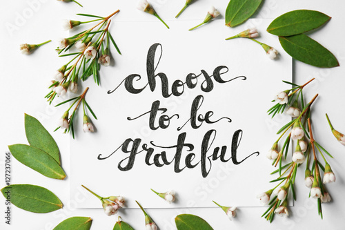 Fotografía  Quote Choose to be grateful written on paper with leaves and flowers on white background