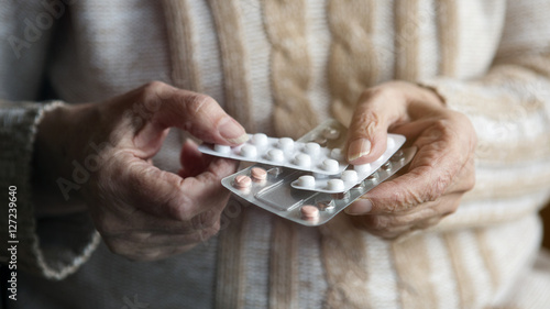Fotografia  closeup of old female hands holding pills