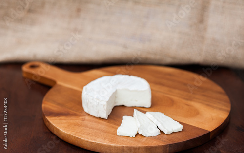Brie or camembert cheese cut out wedge and in slices on a wooden chopping cutting cheese board on dark brown wooden table with a light brown burlap background
