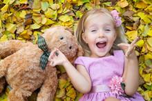 Little Girl Lying On Fallen Leaves In The Street With Teddy Bear