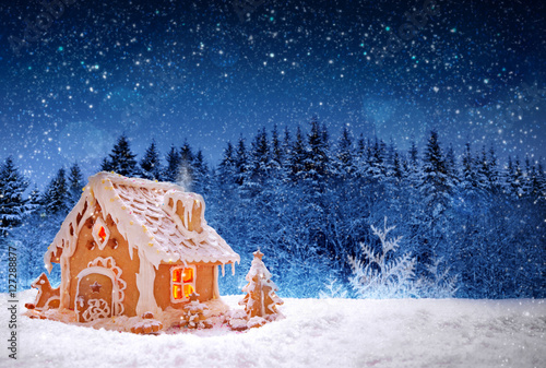 Christmas Gingerbread house and snowfall. Canvas Print