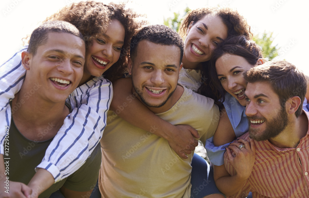 Fototapeta Portrait of six young adult friends piggybacking outdoors