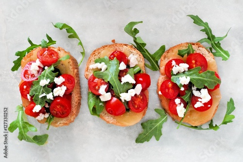 Spoed Fotobehang Voorgerecht Crostini appetizers with cherry tomatoes, arugula, and cheese, above view on white marble