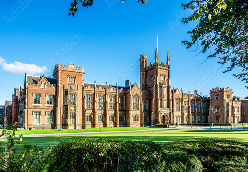 Fotomural The Queen's University of Belfast with a grass lawn, tree branches and a hedge i