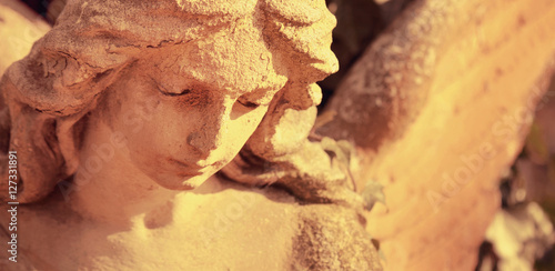Tuinposter Monument Vintage image of a sad angel on a cemetery against the backgroun