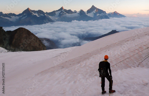 Foto op Plexiglas Alpinisme a mountain climber on a glacier at sunrise in the Swiss Alps with a view of the Mischabel Massif near Seas Fee