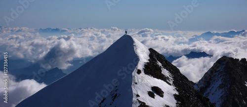 In de dag Alpinisme a mountain climber on the summit of a high alpine peak in the Swiss Alps near Zermatt