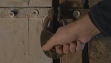 Male Metal Key Unlocks The Padlock, Opens The Wooden Door And Enters