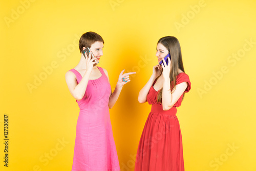 Fotografija  Technology, friendship and leirure concept - two smiling young women talking with smartphones