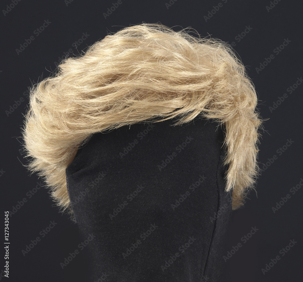 Fototapeta blonde feminine wig on black background and textile mannequin.