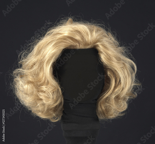 Foto blonde feminine wig on black background and textile mannequin.