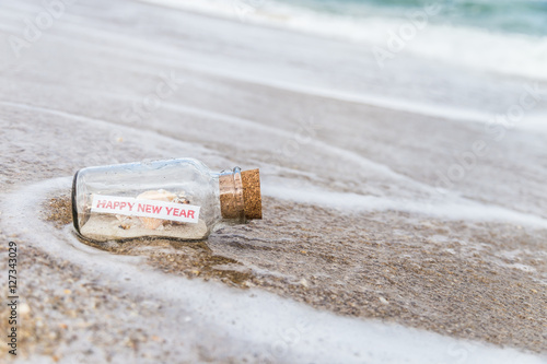 Fotografie, Obraz  message in a bottle/bottle with a message happy new year on sandy beach in Florida