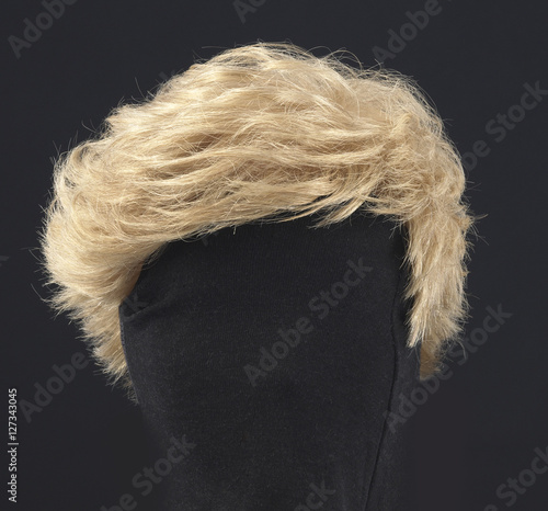 blonde feminine wig on black background and textile mannequin. Fotobehang