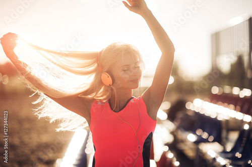 Foto  Portrait of a sporty adolescent girl resting from exercising, using listening to music with headphones, smiling outdoors