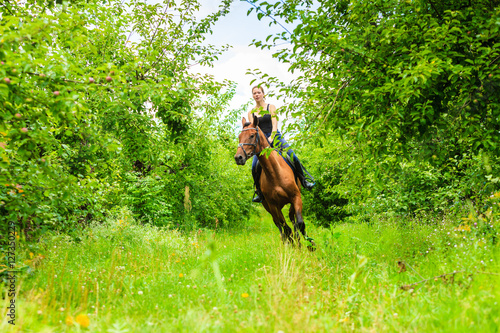 Foto auf AluDibond Reiten Young woman ridding on a horse