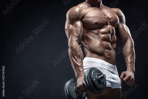 Fotografie, Obraz  Muscular bodybuilder guy doing exercises with dumbbell