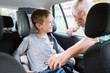 Grandfather Buckling Up On Grandson In Car Safety Seat