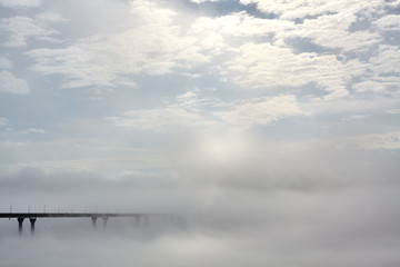Fototapeta Industrialny the bridge goes into the morning mist fog