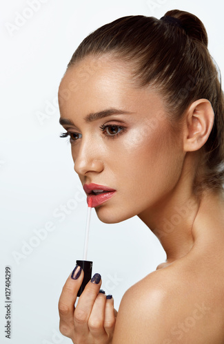 Beautiful Woman Doing Makeup Using Lip Gloss On Lips. Cosmetics Poster
