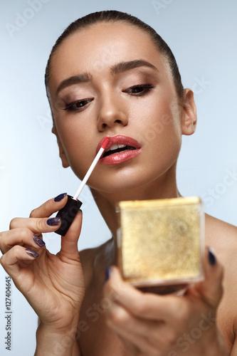 Poster  Beautiful Woman Doing Makeup Putting Lipgloss On Lips. Cosmetics