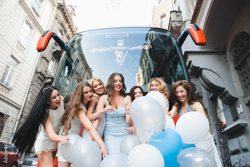Photo  The girls with ballons stand near bus