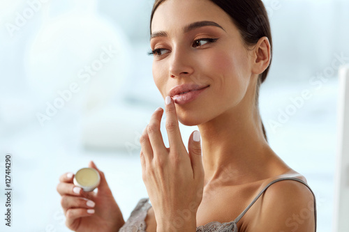 Obraz na płótnie Lips Skin Care. Woman With Beauty Face Applying Lip Balm On