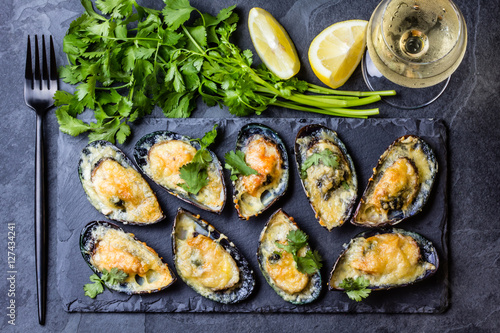 Coquillage Seafood. Baked mussels with cheese and lemon in shells