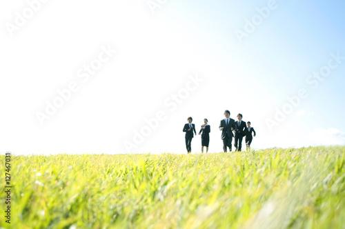 Valokuva  草原を走るビジネスマンとビジネスウーマン