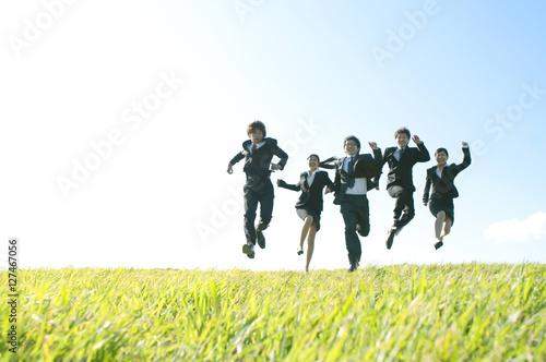 Fotografia  草原でジャンプをするビジネスマンとビジネスウーマン