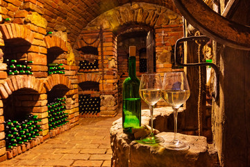 FototapetaSmall wine cellar with bottle and glasses of wine