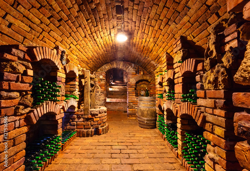 Leinwand Poster Small wine cellar with bottles and keg