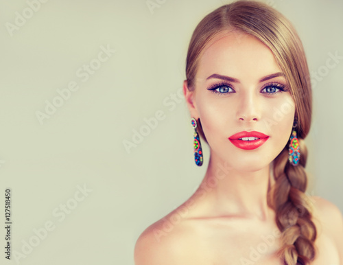 Beautiful young woman  with braid and red lips . Fashion jewelry ,beauty  earrings