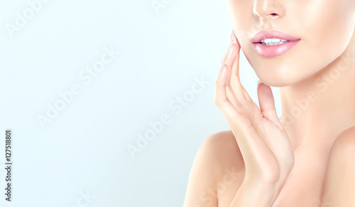 Fototapeta Beautiful Young Woman with clean fresh skin  touch  face . Facial  treatment  , cosmetology , beauty  and spa .