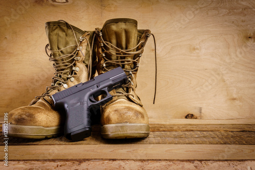 used brown military boots and a gun on a wooden table - Buy this