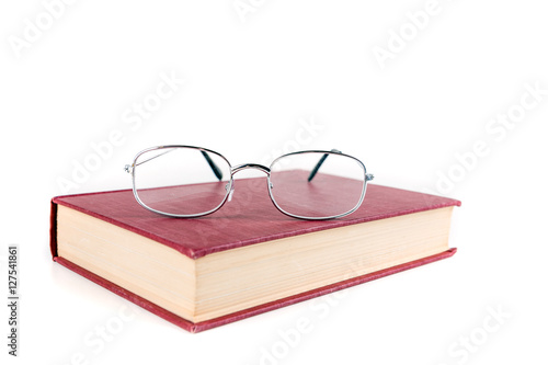 Valokuva  Book with reading glasses isolated on white background