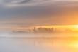 Orange sunrise over a misty wild river